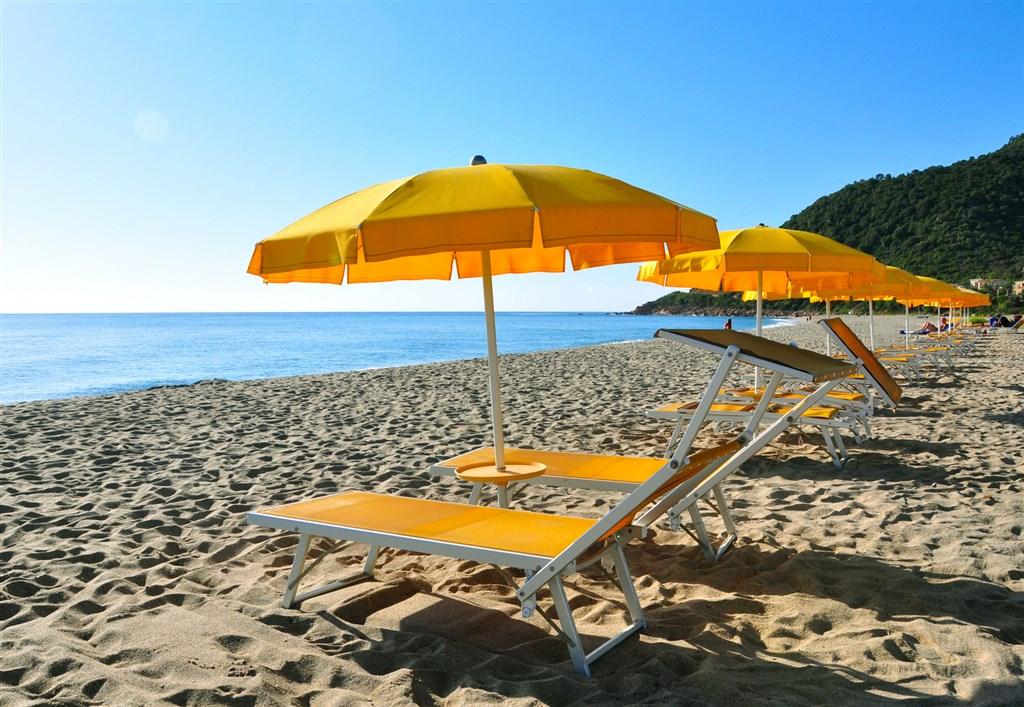 Pláž s lehátky a slunečníky, Ogliastra, Sardinie